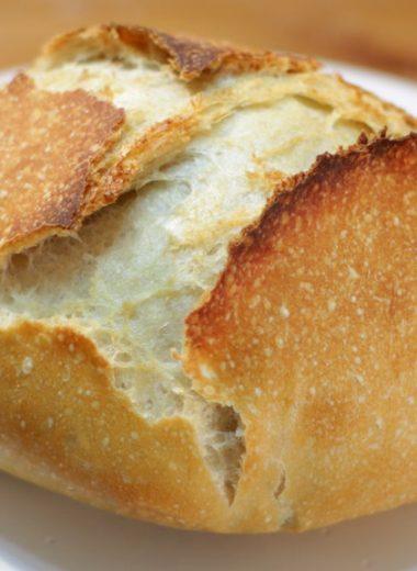 No knead bread on a white cake pedestal