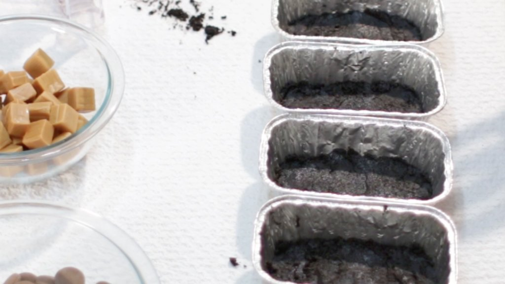 Oreo cookie base pressed into 4 small aluminum bread pans.