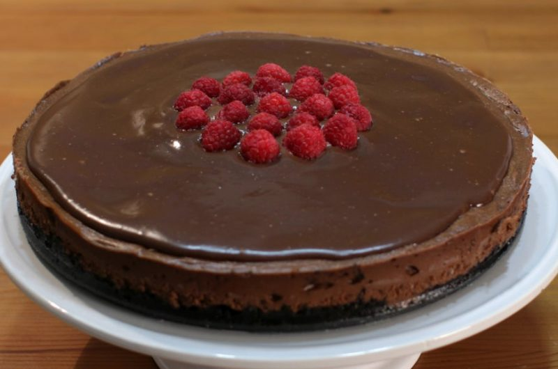 Triple chocolate cheesecake with raspberries on top of a white cake pedestal.