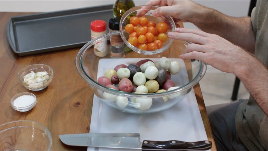 Baby potatoes, onions, and tomatoes added to a large glass bowl.