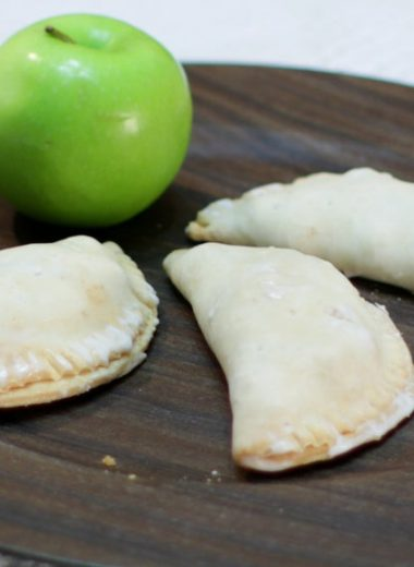 Three apple hand pies and a green apple on a brown plate.