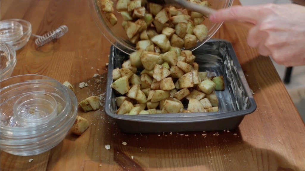 Hand pouring in a bowl full of apples into an 8x8 buttered pan.