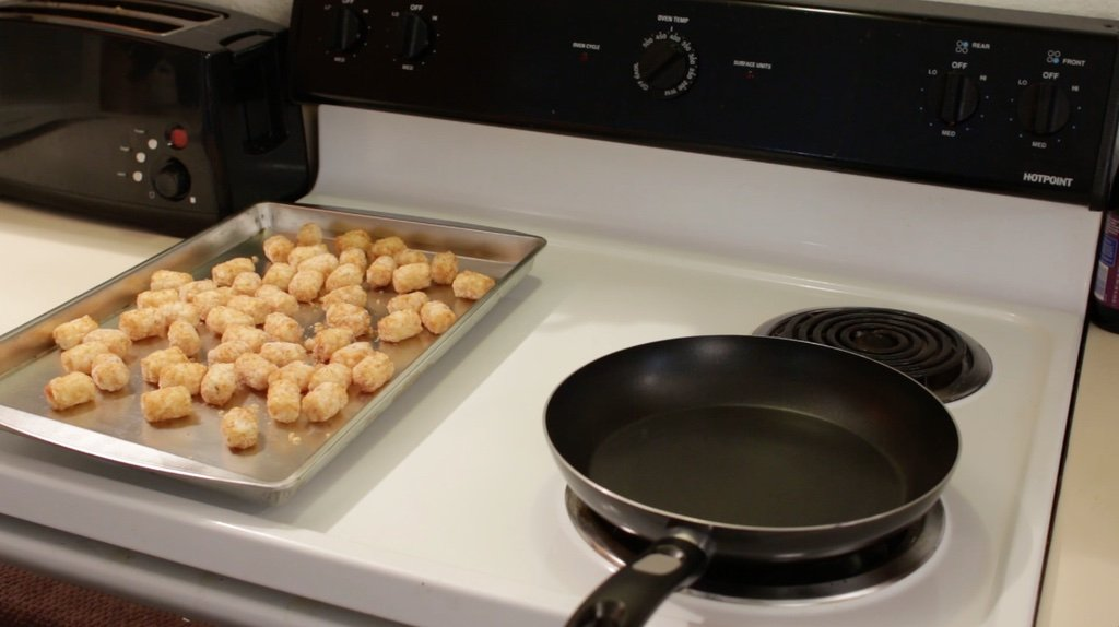 Sheet pan full of frozen tater tots on top of an oven.