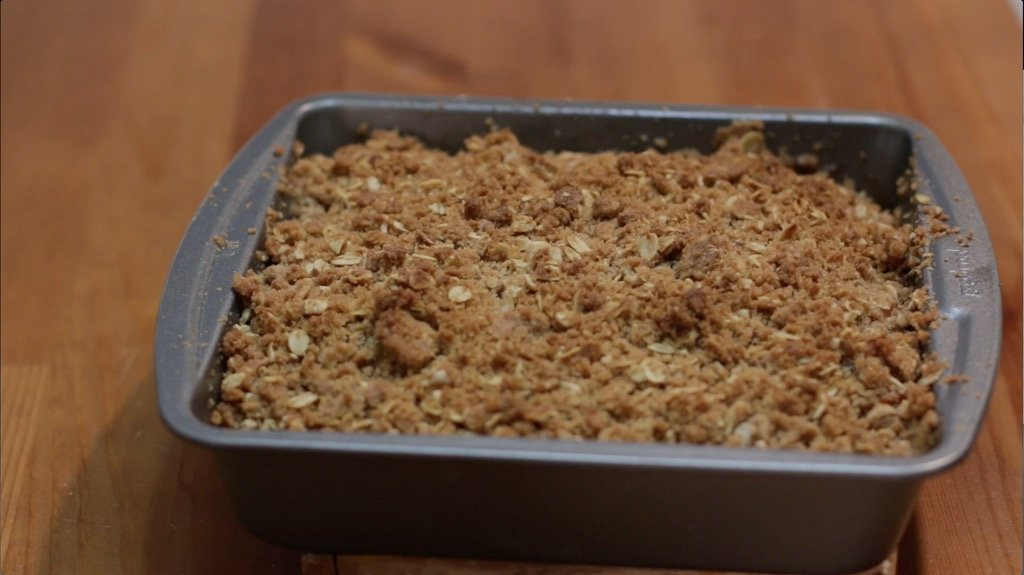 Pan with a baked apple crisp in it sitting on a wooden table.