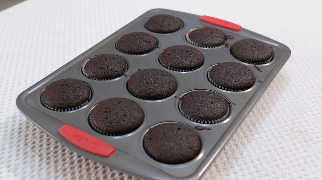 Freshly baked chocolate cupcakes still in the pan.