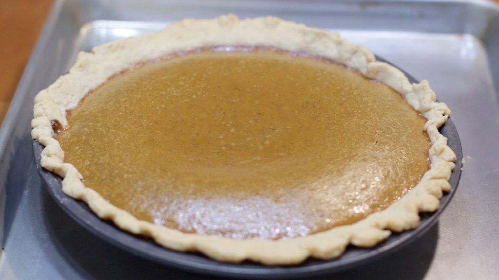 Freshly baked homemade pumpkin pie on a sheet pan.