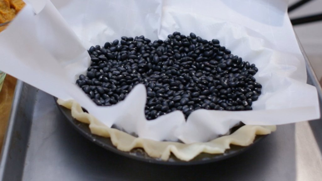 Black beans on a parchment paper an unbaked pie crust.