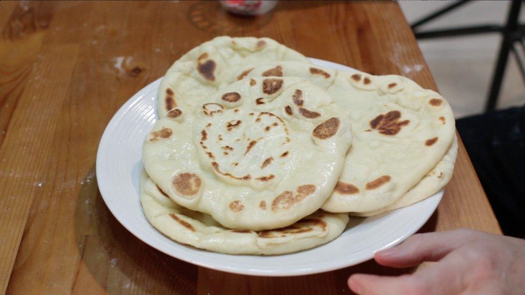 White plate full of fresh homemade naan.