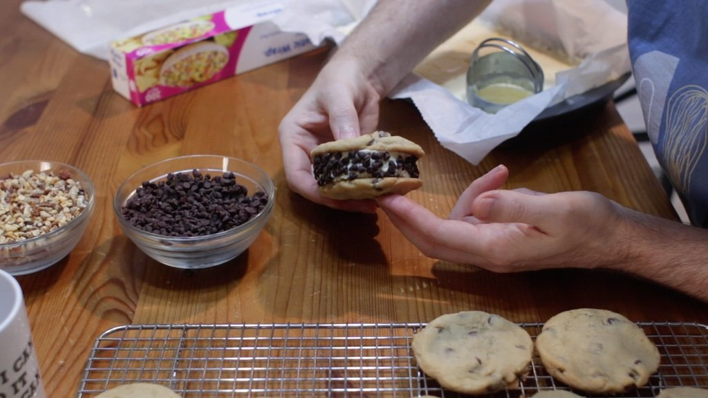 Hand holding a homemade chipwich with chocolate chip cookie and mini chocolate chips
