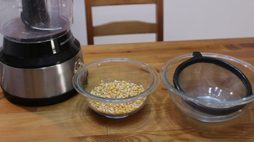 Popcorn kernels in a glass bowl next to a food processor.