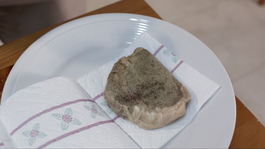 Piece of grey looking steak on a plate with paper towel.