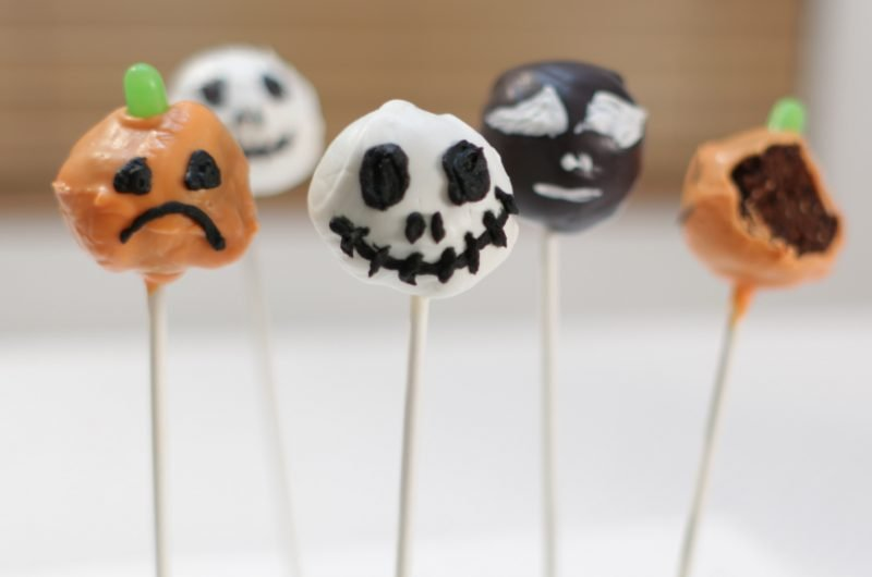 Brownie pops decorated with a Halloween theme on a table.
