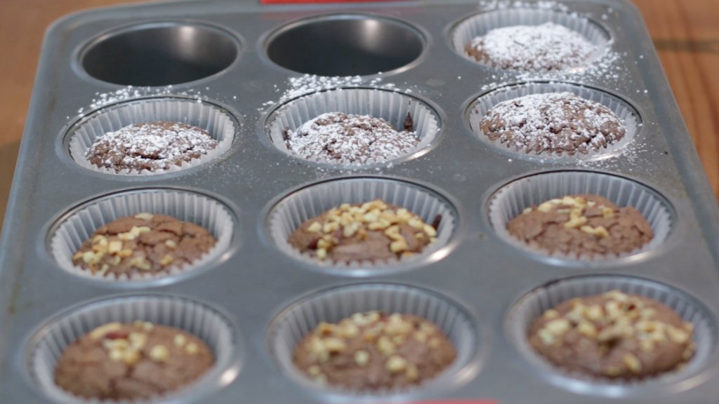 Muffin pan filled with freshly baked Nutella brownies with nuts and powdered sugar on top.
