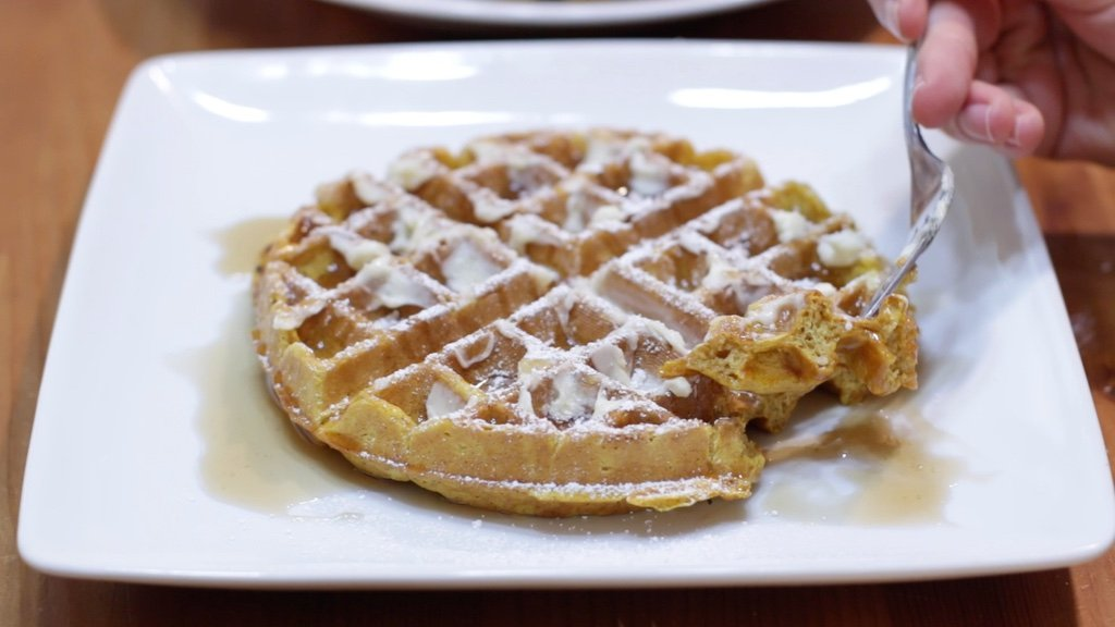 Freshly made homemade pumpkin waffle on a white plate covered with butter, maple syrup, and powdered sugar.