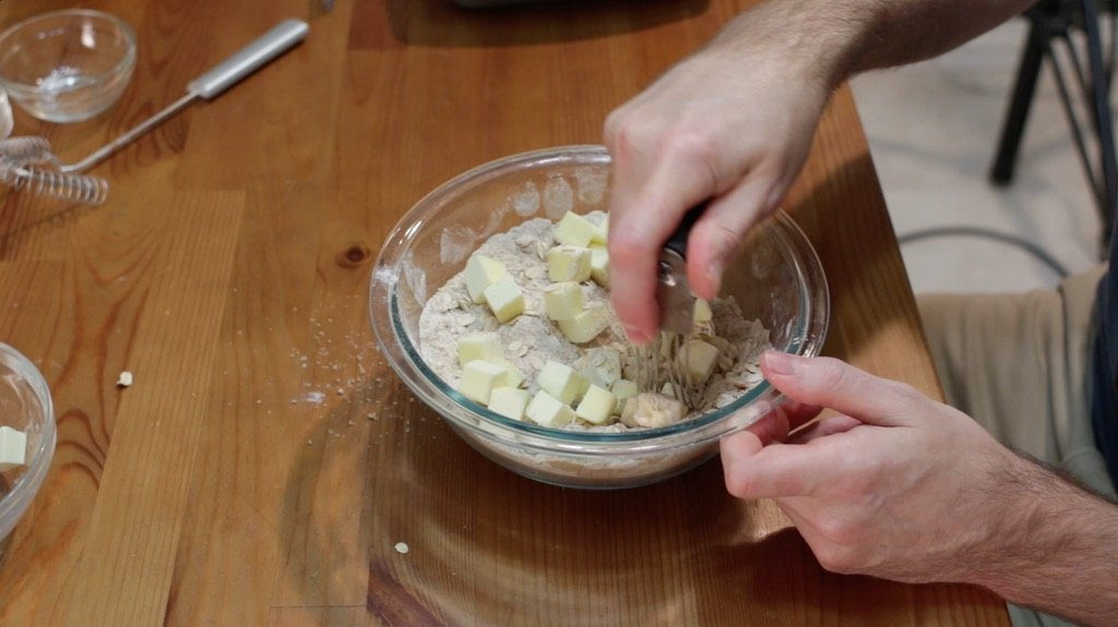 Hand with pastry blender mixing in the cubed butter with the sugar and flour mixture to create the crumble.