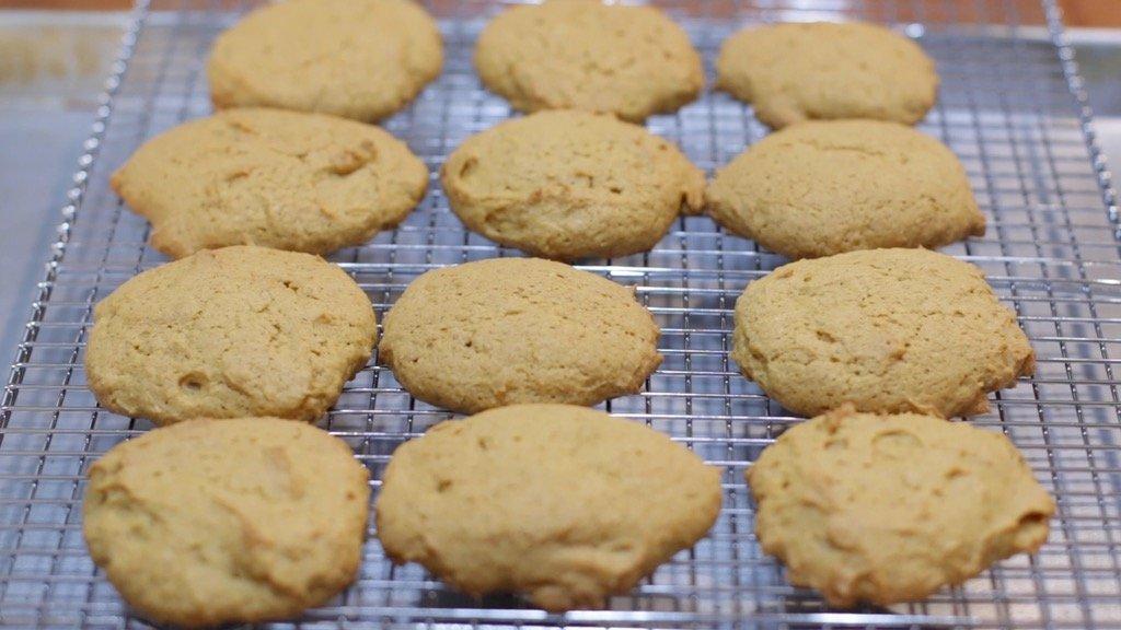 Twelve freshly baked pumpkin cookies on a wire rack.