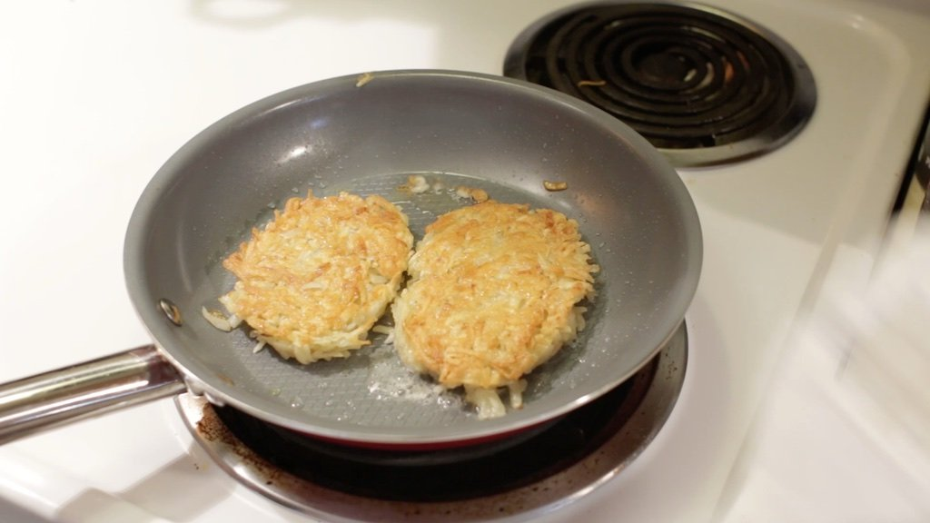 Two homemade hash browns frying in a skillet.