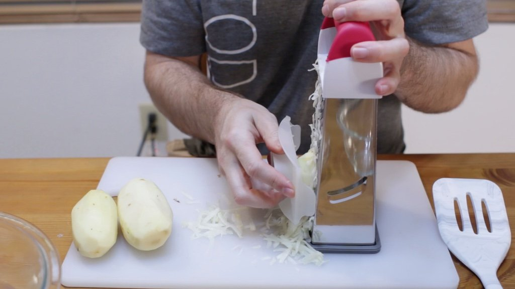 Hand grating potatoes with a box grater.