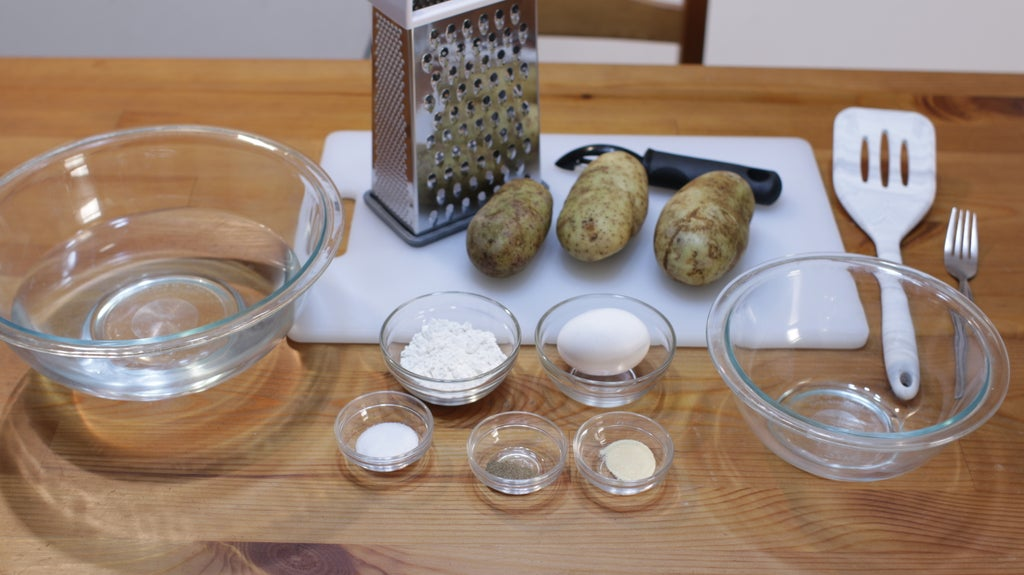 Box grater, potatoes, egg, flour, and other ingredients in glass bowls on a wooden table.