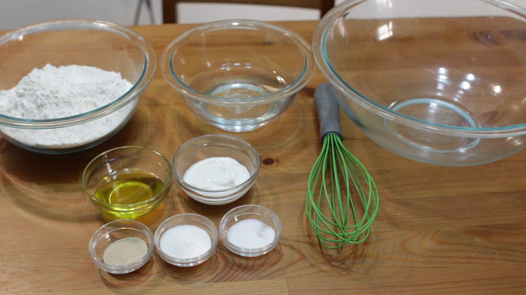 Flour and other ingredients in glass bowls on a wooden table.