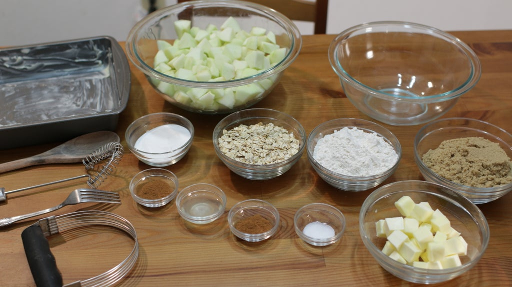 Apples, oats, sugar, flour, butter, and spices in glass bowls on a table.
