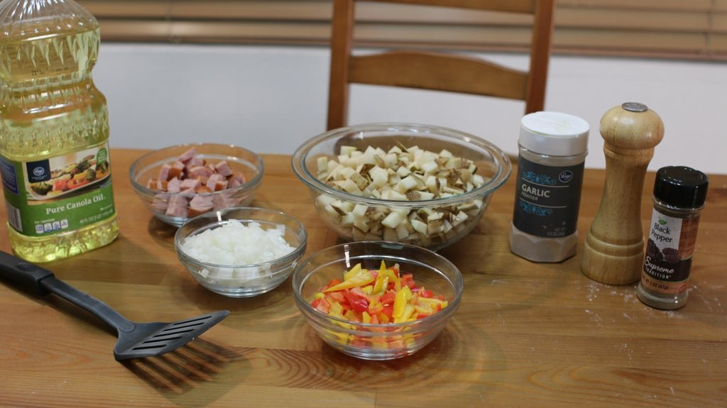 Diced potatoes, peppers, onions, and kielbasa sausage in glass bowls on a wooden table.