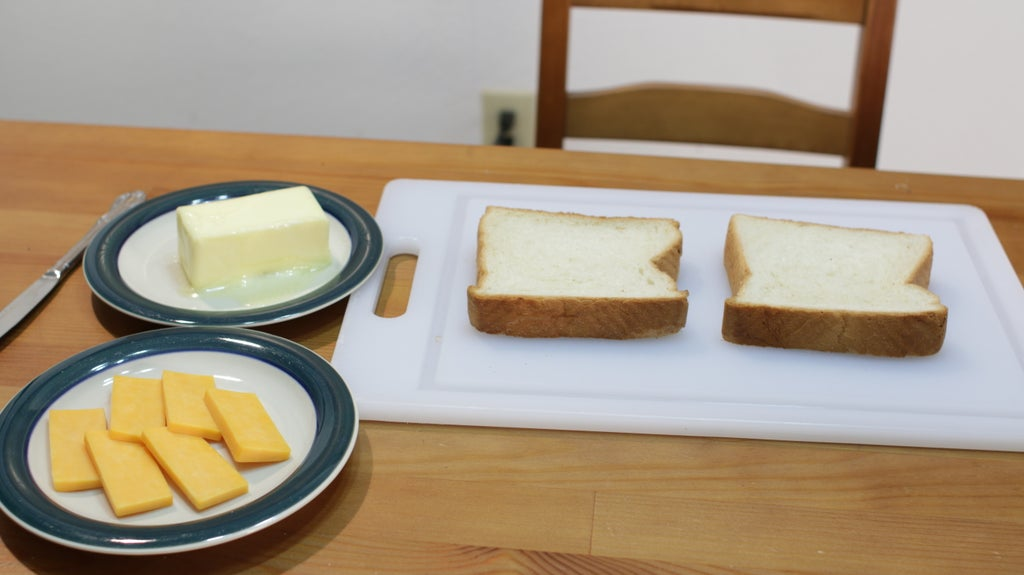 Two thick slices of white bread next to a plate of cheese and butter.