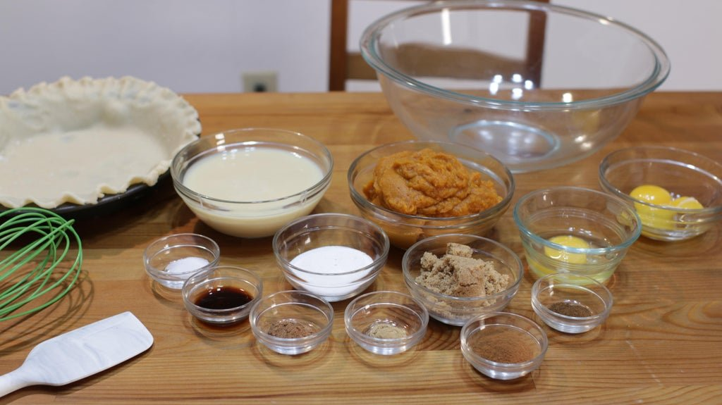 Several ingredients in glass bowls on a wooden table, including pie crust, pumpkin puree, eggs, sugar, etc.