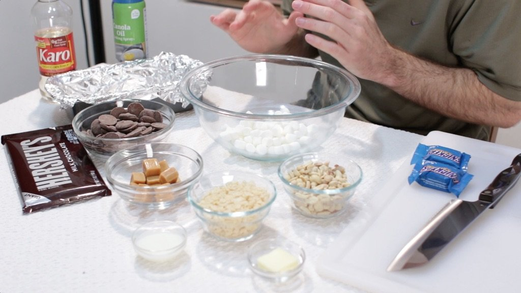 Several of ingredients in glass bowls on top of a white table such as peanuts, caramel, chocolate, marshmallows, etc.