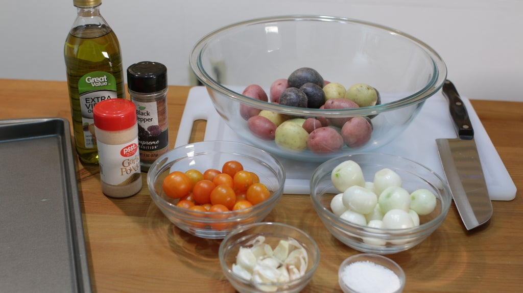 baby potatoes, pearl onions, cherry tomatoes, garlic, and salt in glass bowls on a table.