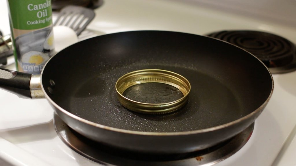 Mason jar lid ring on in a skillet sprayed with cooking spray.