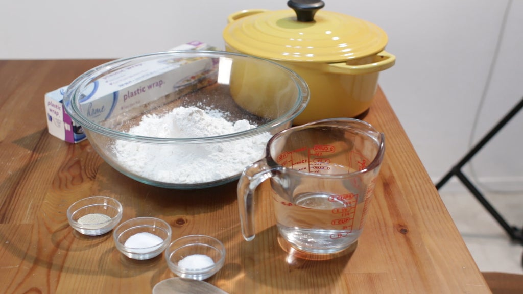 Yellow dutch oven, flour, water, and other ingredients in bowls on a table.