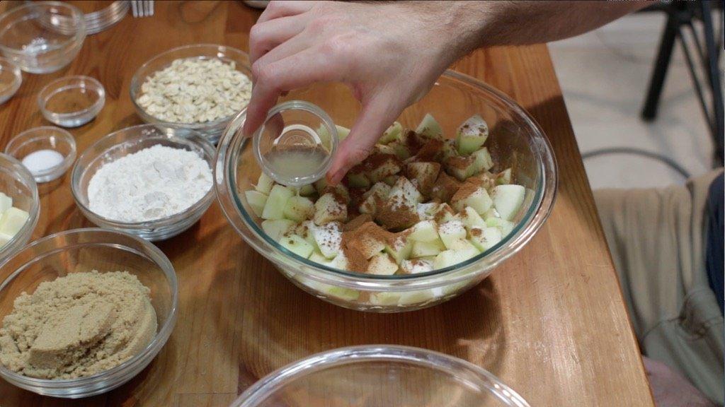 Cinnamon, sugar, lemon juice and apples in a glass bowl.
