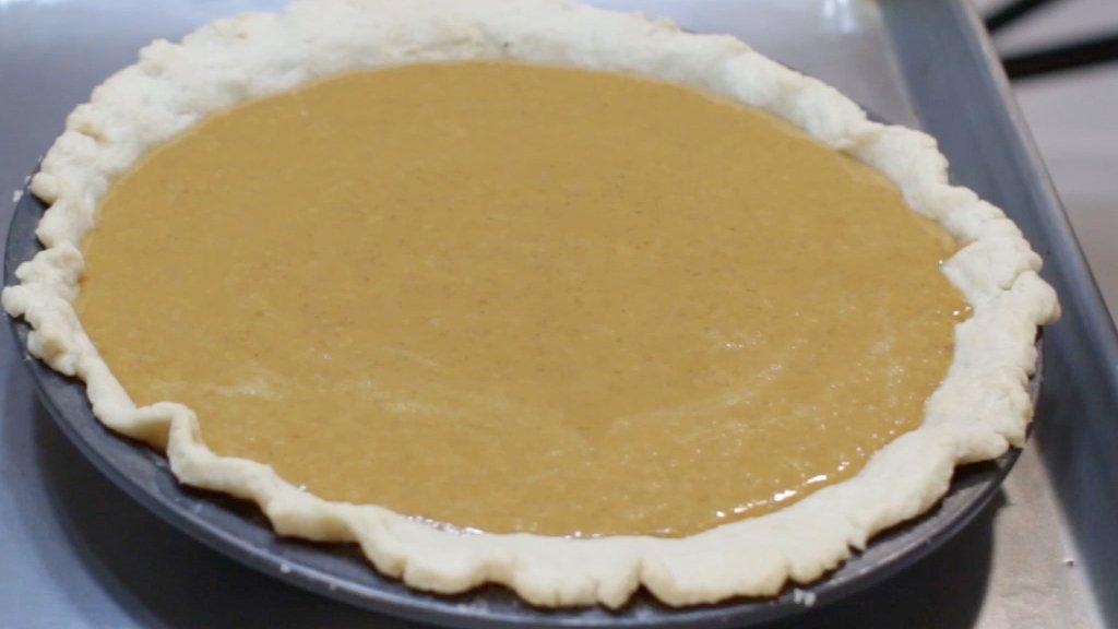 Unbaked homemade pumpkin pie on a sheet pan.
