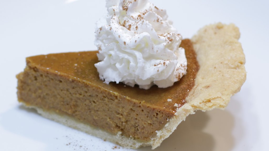 Slice of pumpkin pie with whipped cream on a white plate.