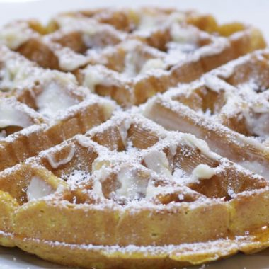Pumpkin waffles on a white plate with butter, maple syrup, and powdered sugar.