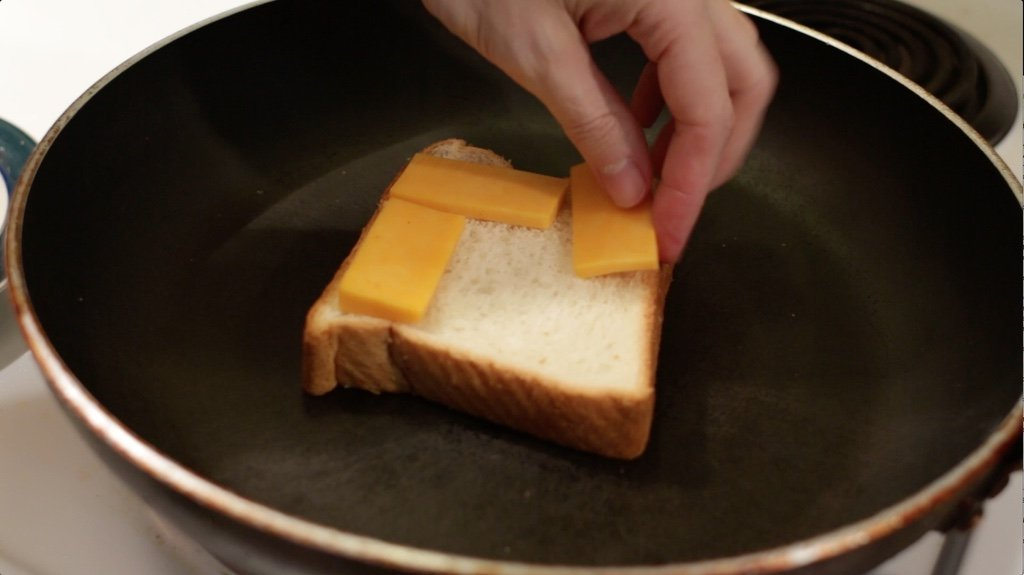 Hand adding slices of cheddar cheese to a slice of white bread in a skillet.