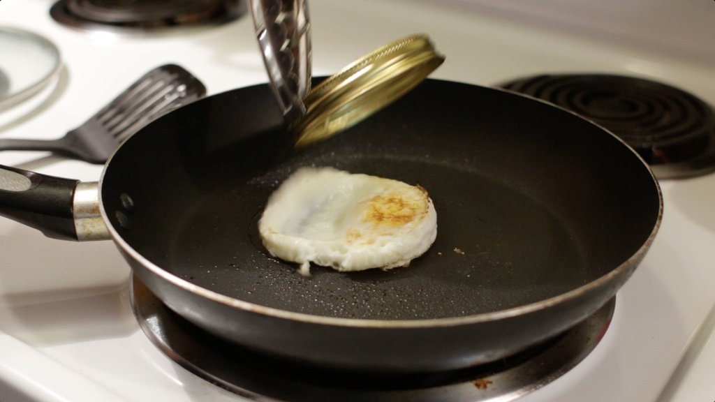 Tongs removing mason jar lid ring from the cooked egg in the skillet.