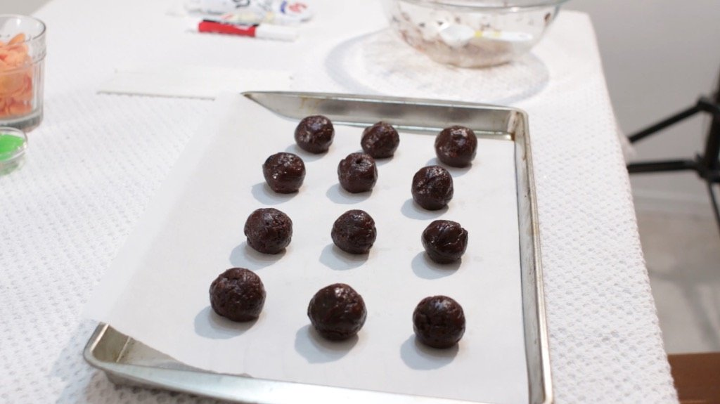 Several brownie pop balls on a sheet pan lined with parchment paper.