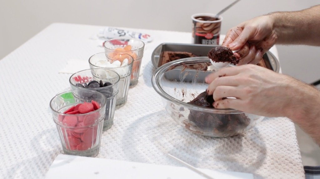 Hand scooping brownie mix out of a large glass bowl with a tablespoon.