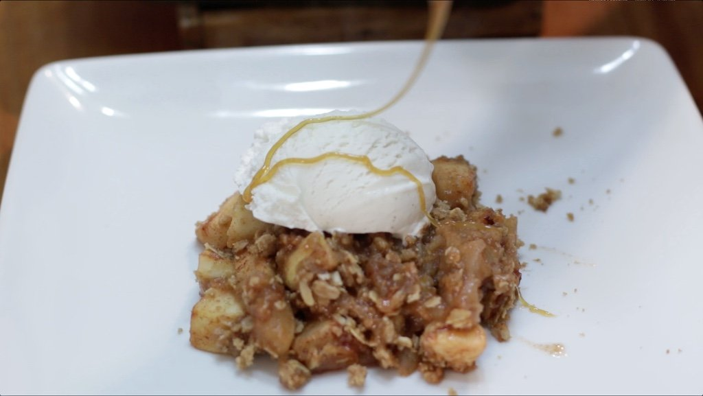 Drizzle of caramel being poured on top of a scoop of ice cream and apple crisp.