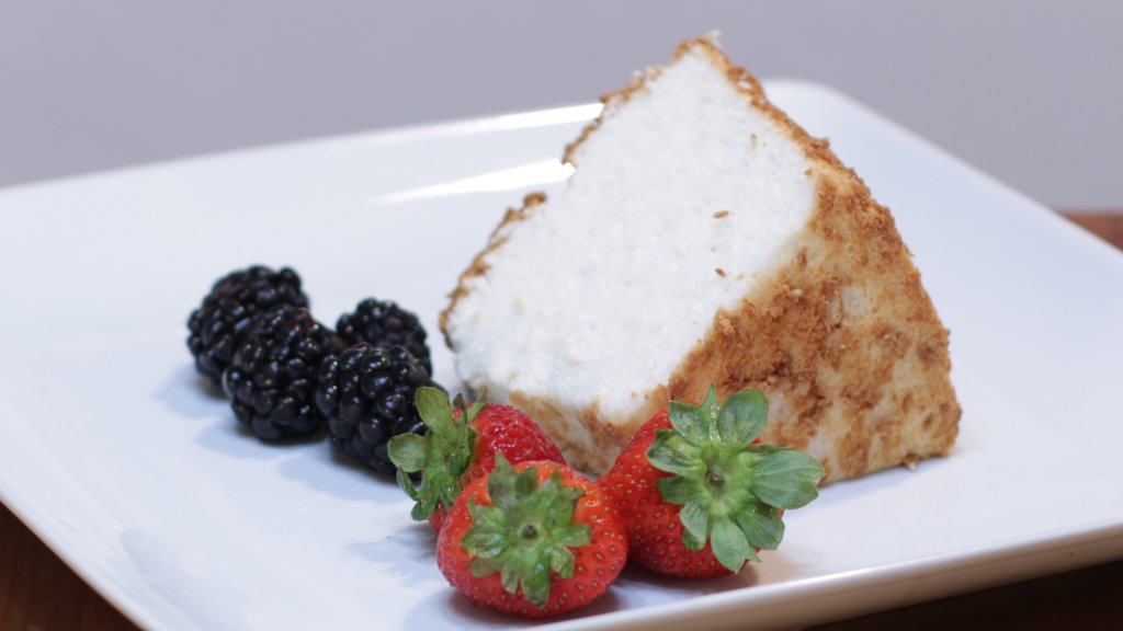 Slice of angel food cake on a white plate with strawberries and blackberries.