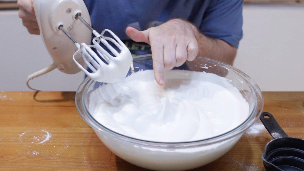 Large glass bowl full of soft peaked egg whites for angel food cake batter.