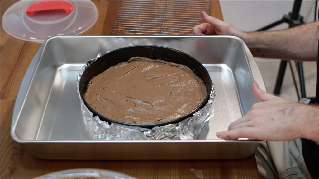 Chocolate cheesecake in springform pan covered with foil in a roasting pan.