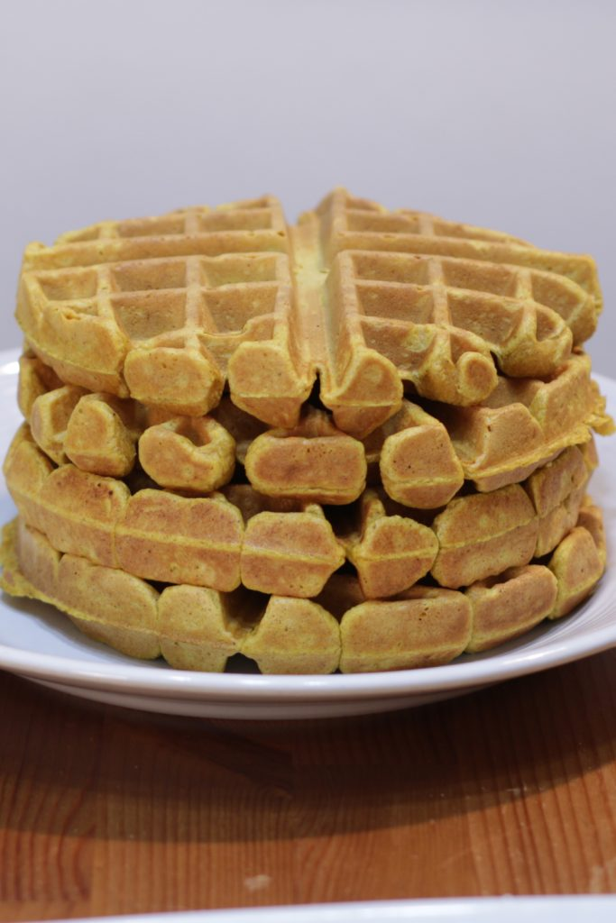 Stack of four thick pumpkin waffles on a white plate.
