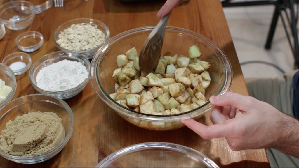 Medium glass bowl full of green apples covered in a sugar and cinnamon mixture.