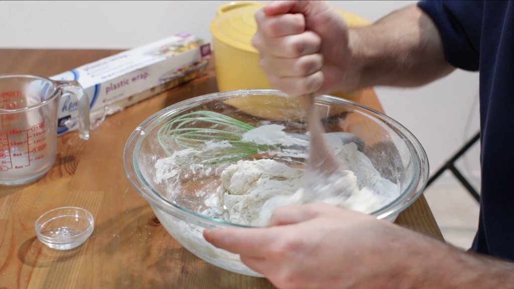 Hand stirring the no knead bread dough in a large glass bowl.