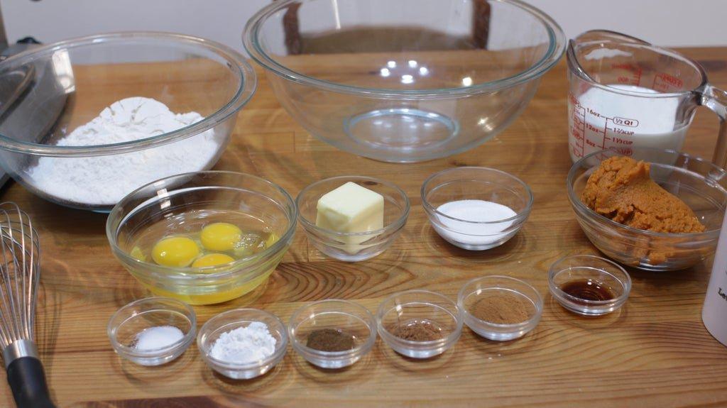 Several glass bowls full of ingredients like eggs, sugar, butter, flour, milk, pumpkin, etc.