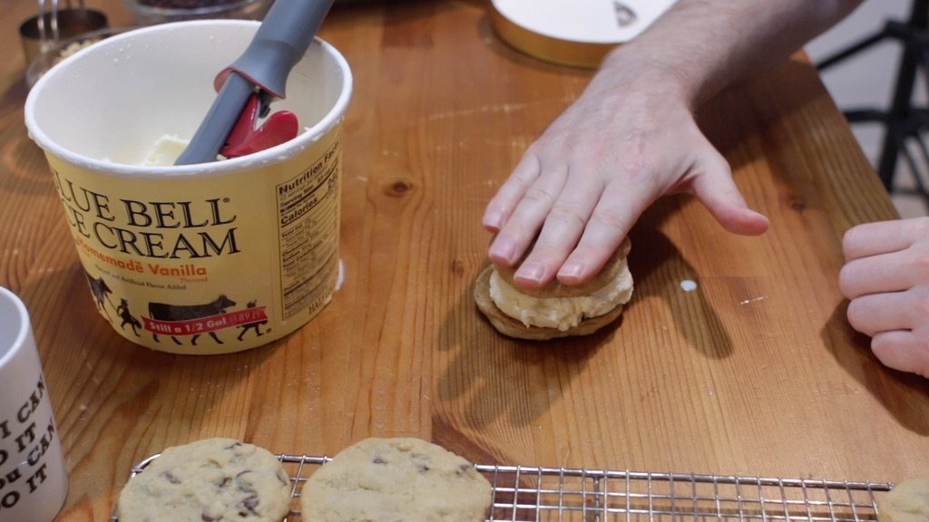 Hand pressing down a cookie on an ice cream cookie sandwich.