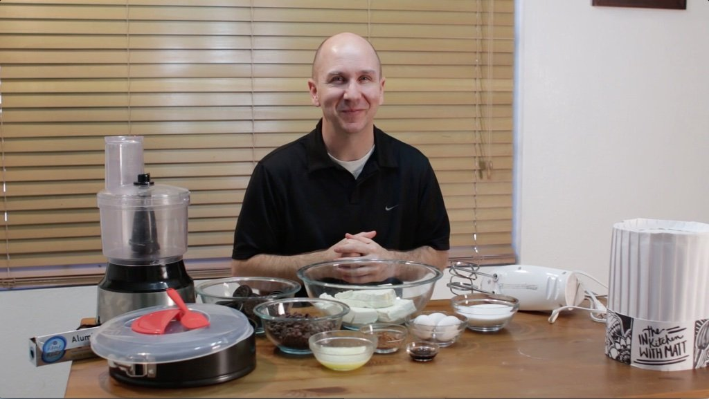Man sitting behind a wooden table full of ingredients in glass bowls.
